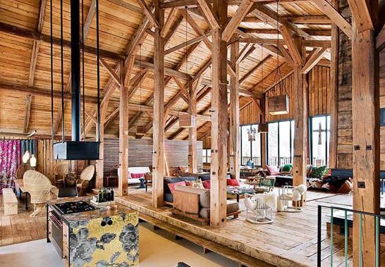 """餐厅 木屋具有空气调节作用。木屋,较一般水泥、砖瓦、轻钢结构住房节能50%~70%,这是美国纽约国家建筑材料实验室的研究结果。因此,木屋又被称为""""世界上唯一真正绿色环保的建筑""""。 设计亮点:站在厨房的角度能将餐厅和休憩的角落都收于眼底。伫立在空间中的木质柱子,排列有序,错落有致,其间夹杂着几盏大大的吊灯。"""