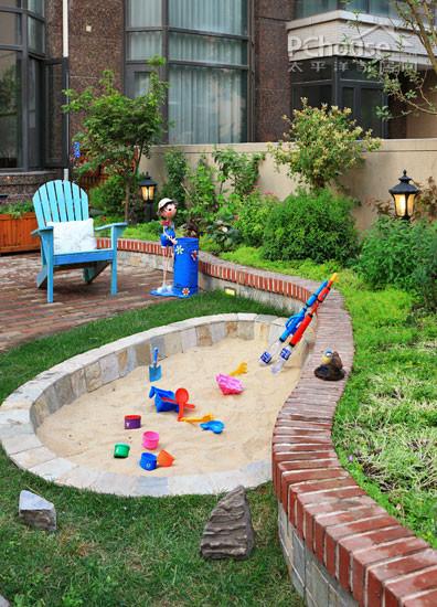 沿着花坛的凹陷处,在草坪上挖出一个半圆形的沙坑,并用柔软的细沙